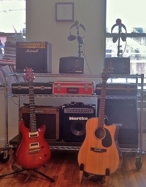 Amps, Mics, and Gear boxes on a wire shelf
