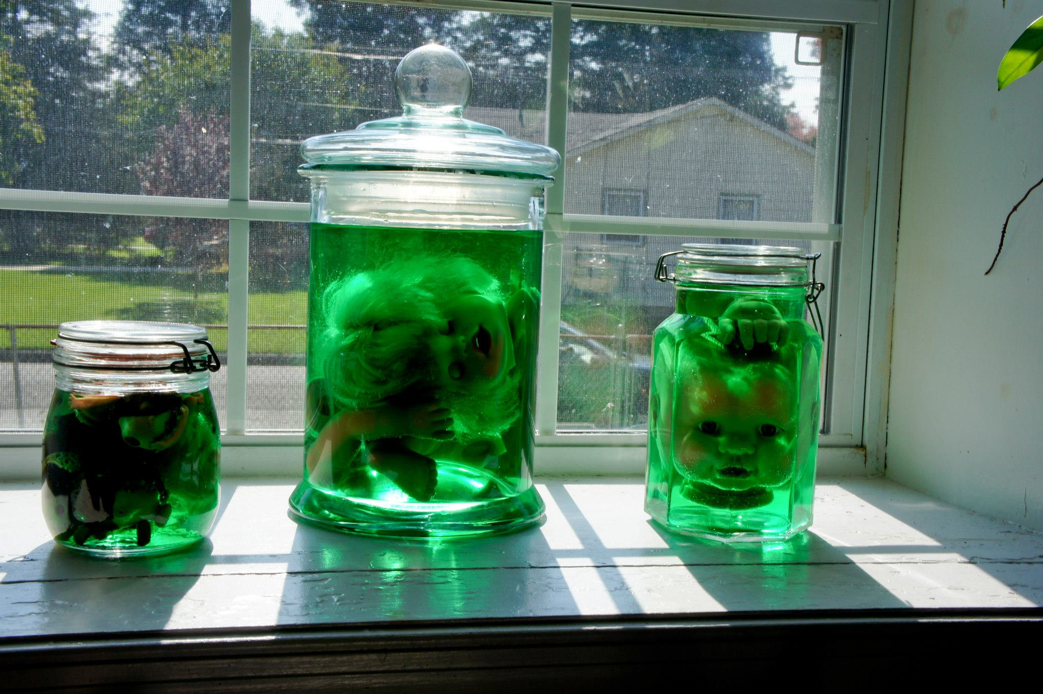 doll heads in jars on shelf - Quick Halloween Decorations