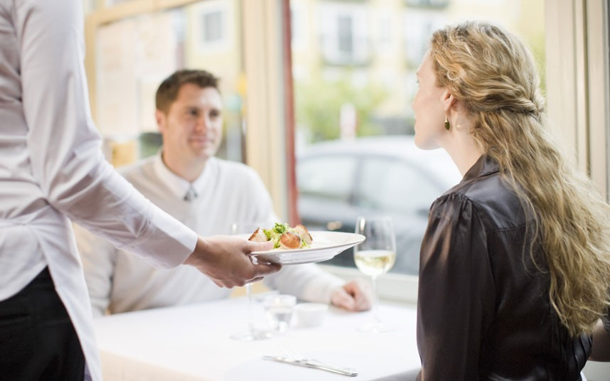 waiter serving guests at restaurant