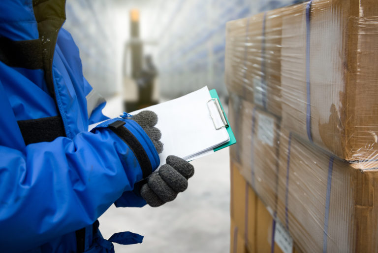 Closeup shooting hand of worker with clipboard checking goods in freezing room or warehouse