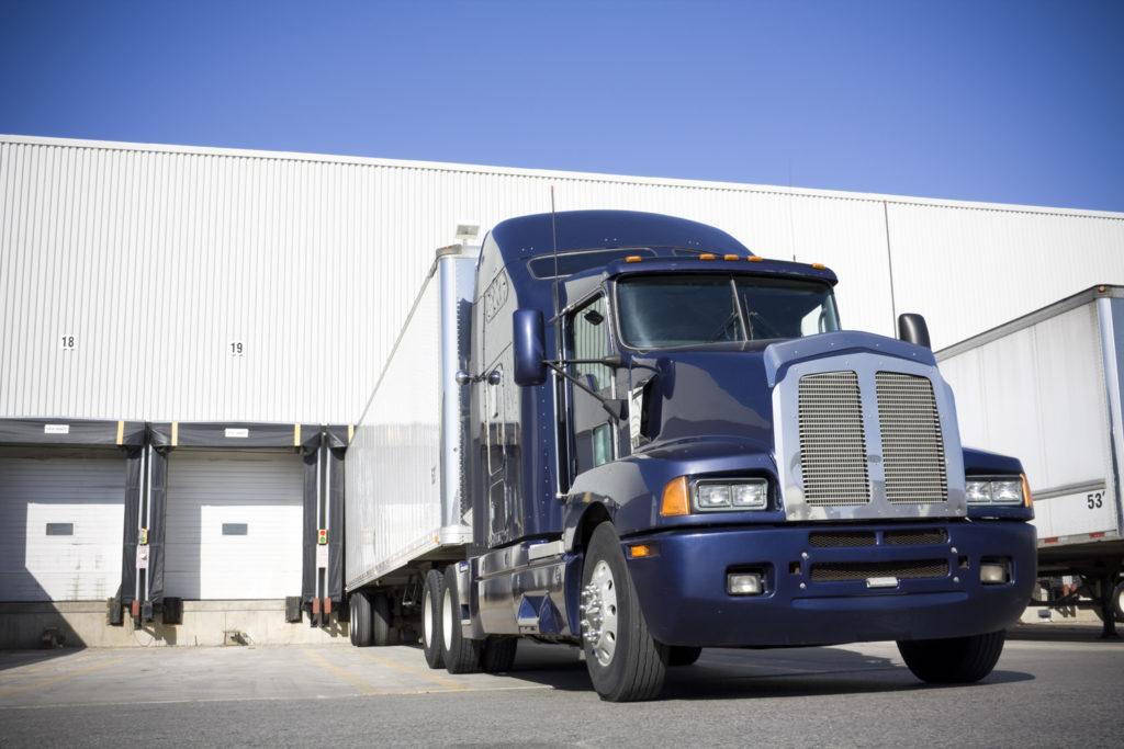 Blue Transport truck docking at warehouse